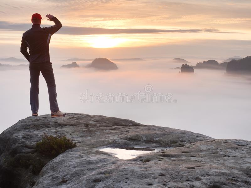 Beautiful moment the miracle of nature. Colorful mist in valley. Man hike. Person silhouette stand. Man stands alone on the peak of rock. Hiker watching to stock photo