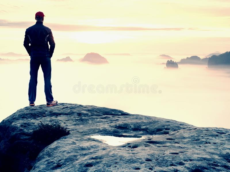 Beautiful moment the miracle of nature. Colorful mist in valley. Man hike. Person silhouette stand. Man stands alone on the peak of rock. Hiker watching to stock images