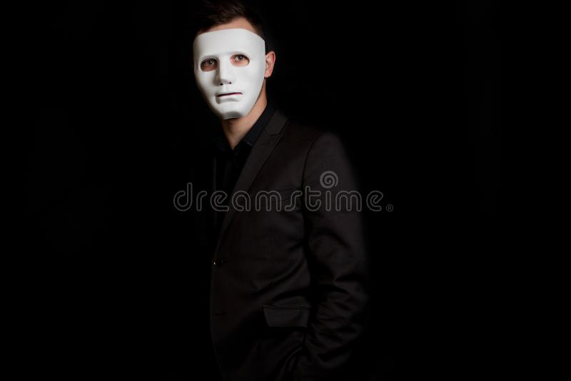 A man stands on a black background in a white mask. Incognito, anonymity.  stock photo