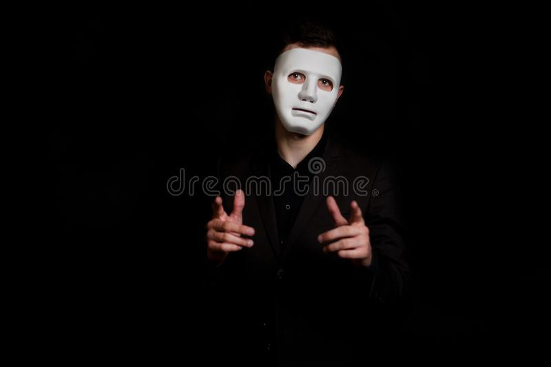 A man stands on a black background in a white mask. Makes a gesture, holding out his hands and pointing with his finger.  stock images