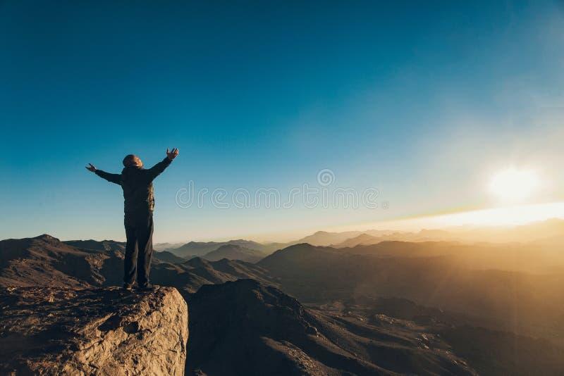 Man stands facing rising sun with lift up his arms on Mount Sinai. Man stands facing rising sun with lift up his arms on Mount Sinai in Egypt stock photos