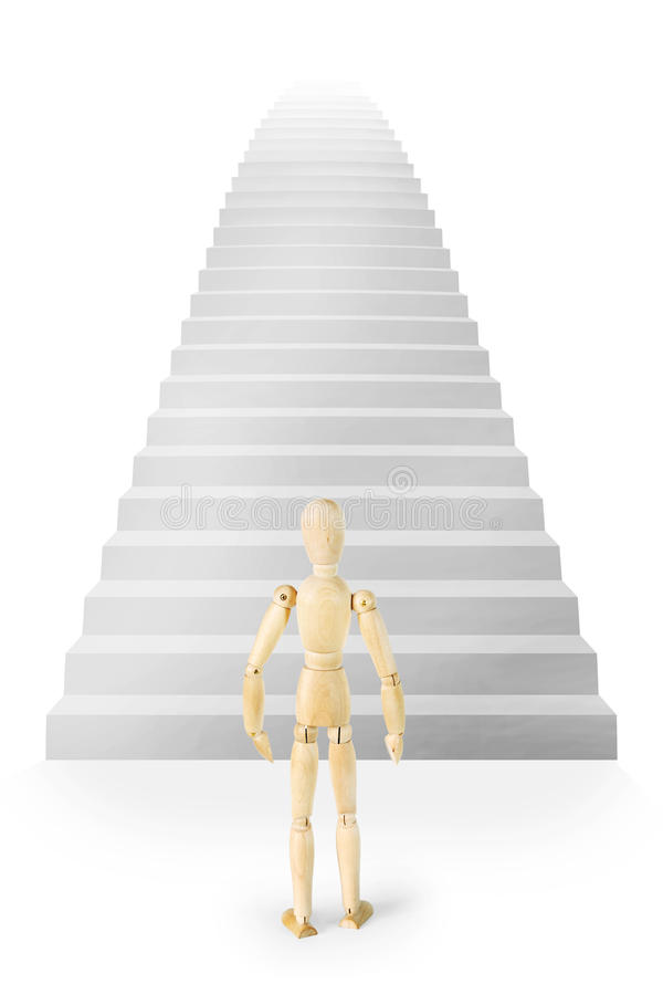 Man stands in front of a very high stairs ascending up. Abstract image with a wooden puppet stock photos