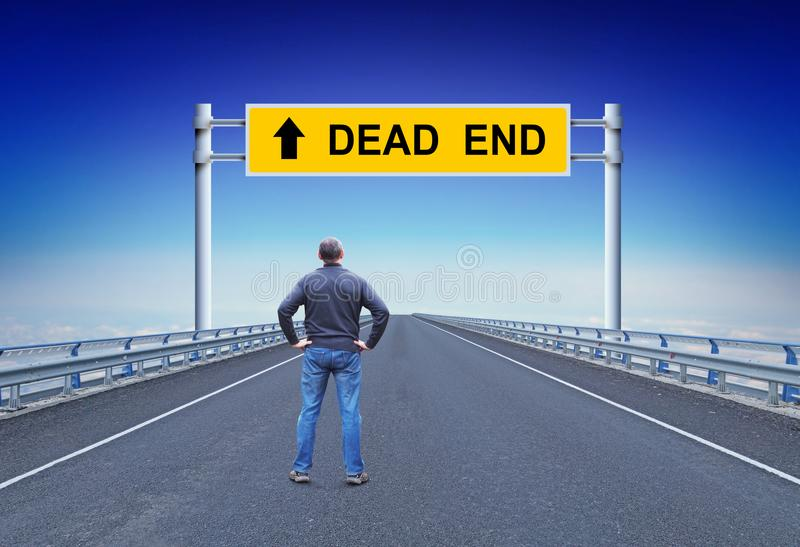 Man stands on a highway in front of road sign with text Dead End. Concept of failure stock photography
