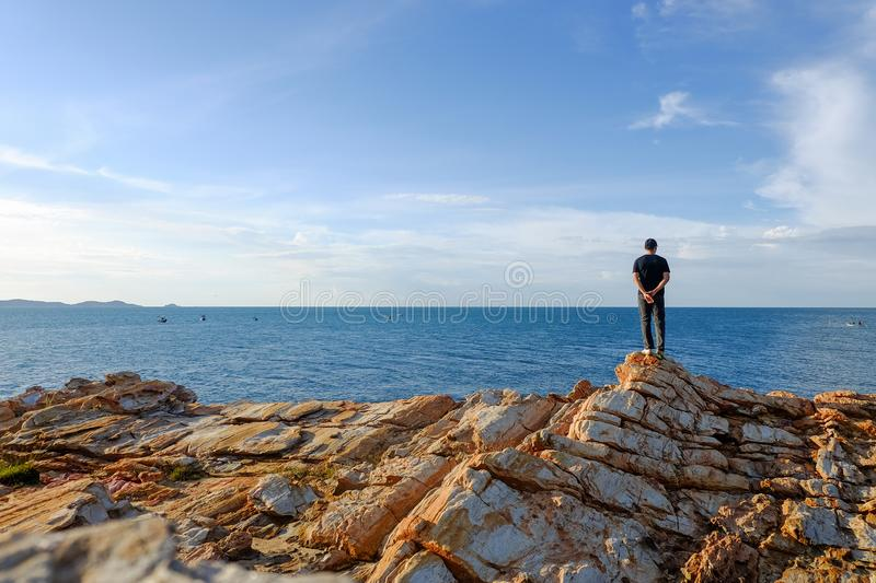 Man stands his arms on a rock. One man stood holding his hand behind him and standing at the viewpoint at Khao Laem Ya, Rayong, Thailand stock photos
