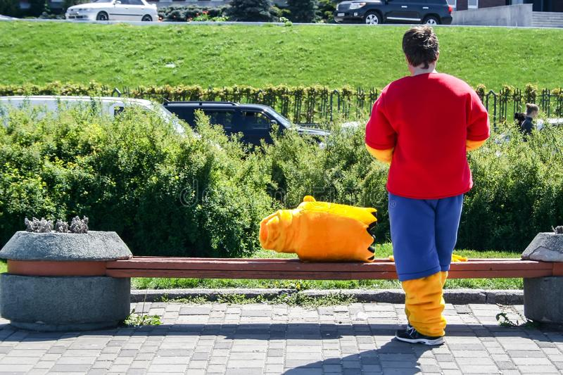 A man stands with his back in a costume of Bart Simpson, whose head lies next to the bench.  royalty free stock image