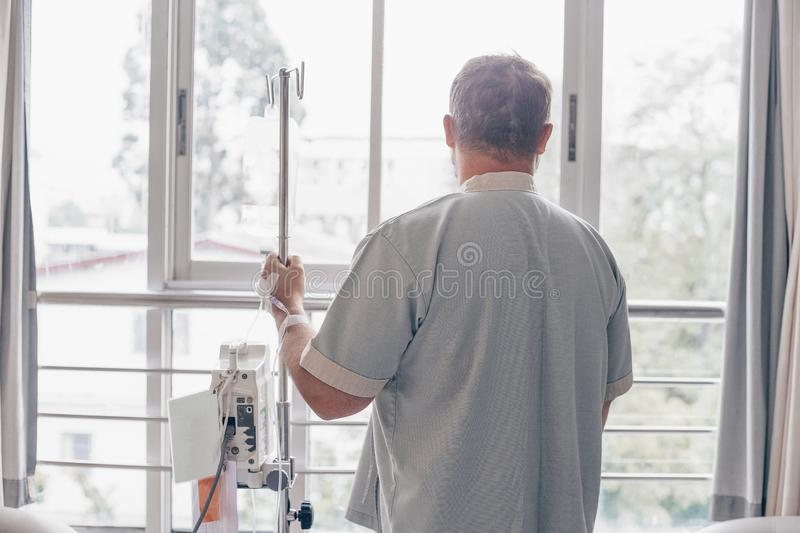 A man stands in a hospital ward and looks out the window. Dropper in a mans hand in a hospital. stock photos