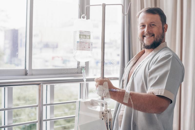 A man stands in a hospital ward and looks out the window. Dropper in a mans hand in a hospital. royalty free stock images