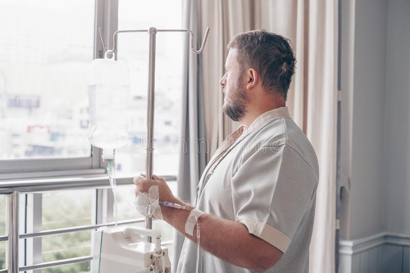 A man stands in a hospital ward and looks out the window. Dropper in a mans hand in a hospital. royalty free stock image