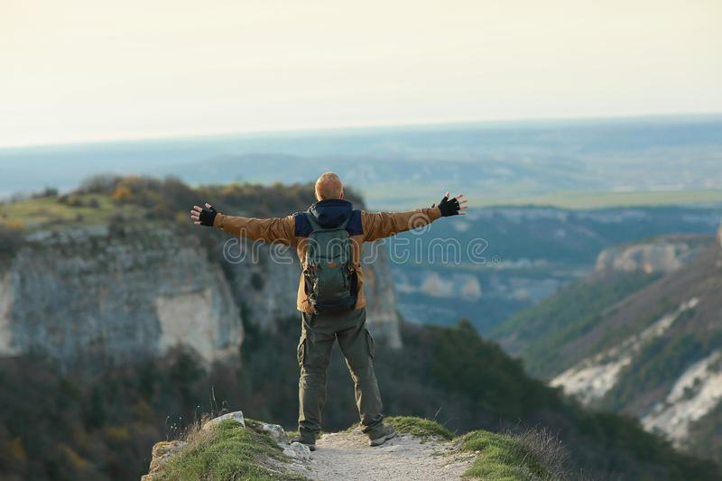 Man stands with open arms on the edge of a cliff in Crimean mountains. A red-haired man in a brown and blue windbreaker with a backpack stands with open arms on royalty free stock photo