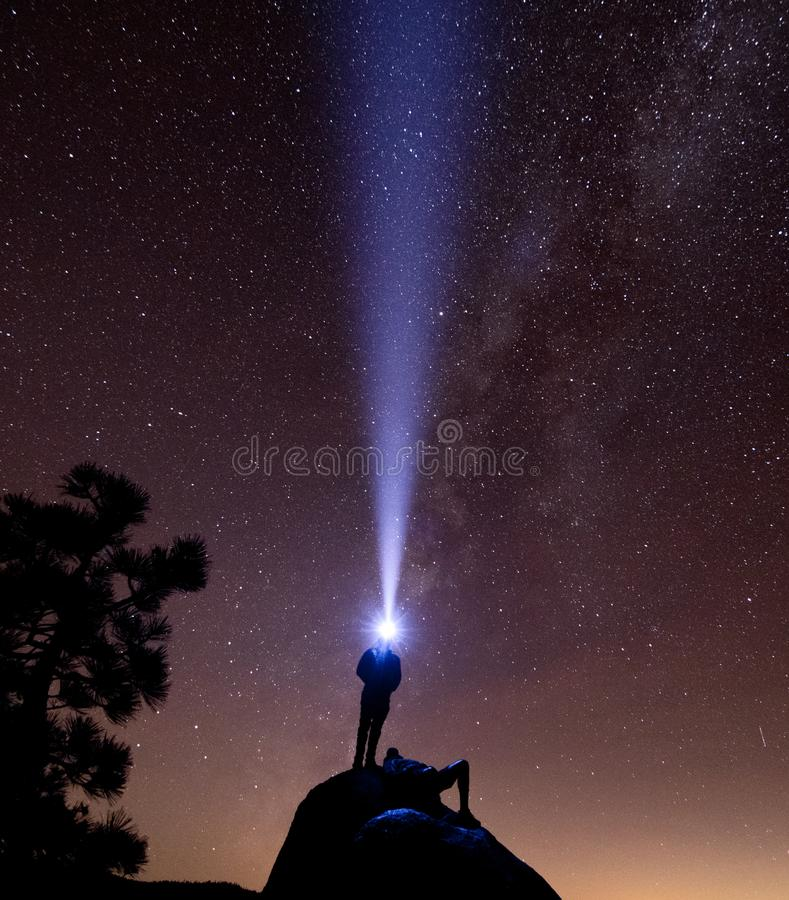 A man stands on a rock with a headlamp while another rests stock images
