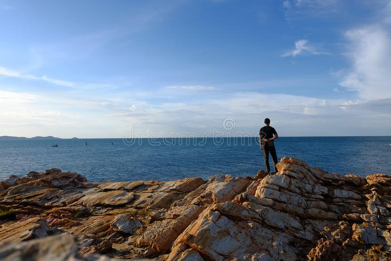 Man stands  on a rock at Khao Laem Ya, Rayong, Thailand. One man put his hand behind him. And make a fight symbol on the rock by the sea at Khao Laem Ya, Rayong stock photos