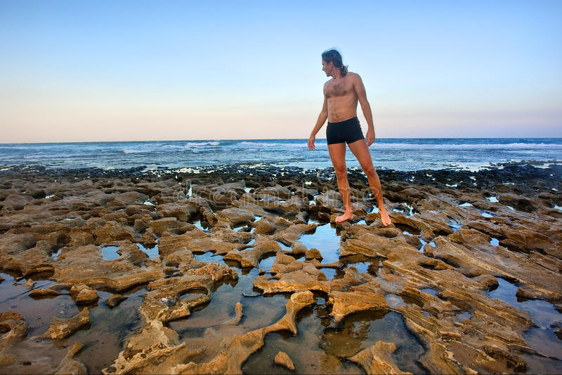Download Man Stands On Rocky Beach Stock Image - Image: 29714451