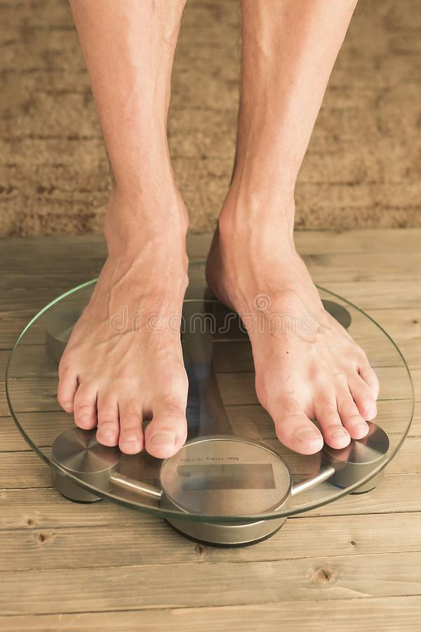 Man stands on the scales. Male feet on glass scales and wooden floor stock image