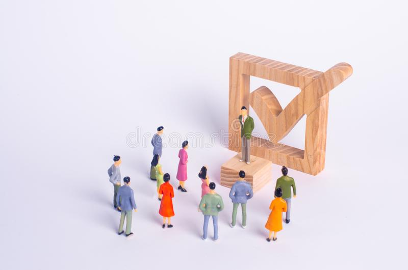 Man stands and shakes people on the background checkbox. The concept of democratic elections, political process, referendum. A person votes in elections. The royalty free stock image