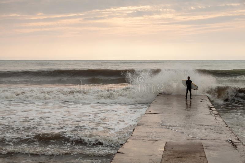 A man stands with a surf in his hands on the beach, overcast, storm stock photo