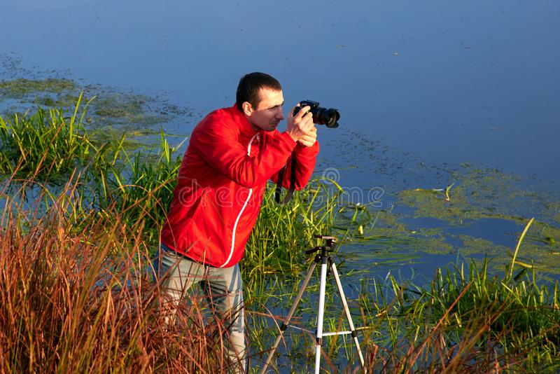 A man stands in a thicket of grass and photographs the river in the autumn morning. A man stands in a thicket of grass and photographs the river in the early royalty free stock image