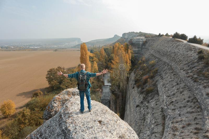 Man stands on the top of a cliff stock photo