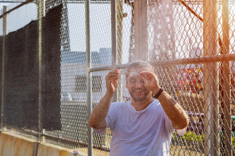 A man stands under a street spray of water and washes his face escaping from the heat royalty free stock photos