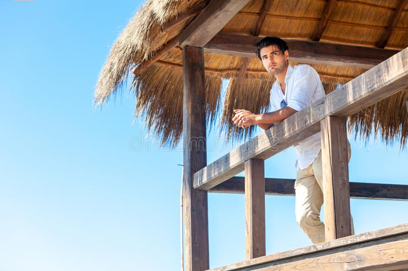 Man stands on wooden hut bungalow at the beach by the sea. Man stands on wooden bungalow structure at the beach by the sea. Elegant and handsome young man with a royalty free stock image