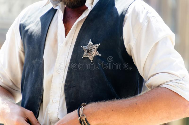 Sheriff star on the vest. A man with the star shaped sheriff badge in his vest. Wild west justice officer and lawman royalty free stock image