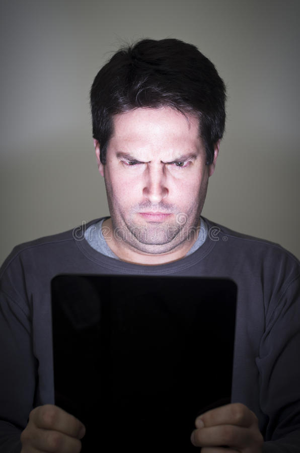 Download Man Stares Intently At A Tablet Device Stock Photo - Image of head, dark: 29474622