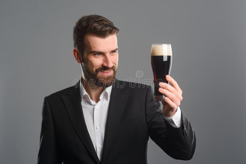 Man staring at beer glass. The beer is excellent: dark brown color of liquid and thick foam of head. Studio shot of satisfied bearded guy in office style stock photos