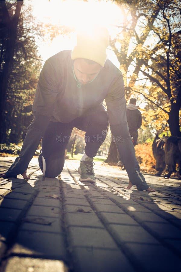 Man start run. On the move. Man start run. Young sporty man exerciser in park. Autumn season stock images