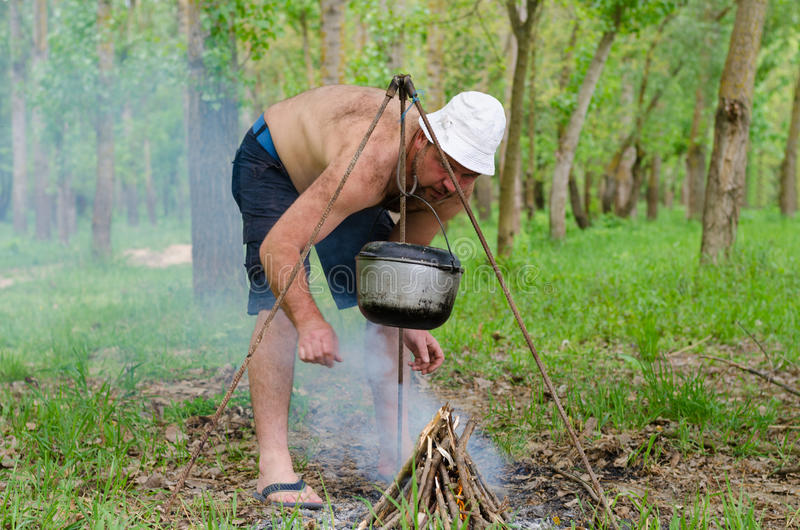 Man starting a cooking fire in a campsite. Shirtless man starting cooking fire campsite lighting the pyramid of kindling as an iron cauldron swings from frame stock image