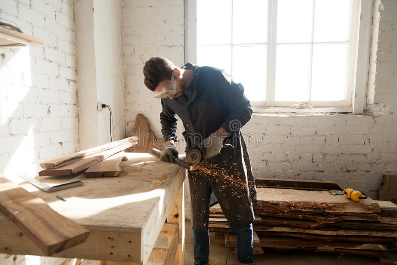 Man starting own small business in home workshop. Worker cutting metal plank with angle grinder in workshop. Young man choosing skilled labor trades as first stock images