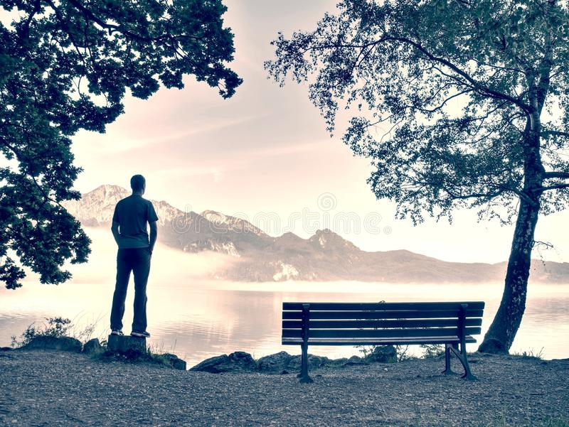 Man stay lonely at the bench in front of the lake royalty free stock image
