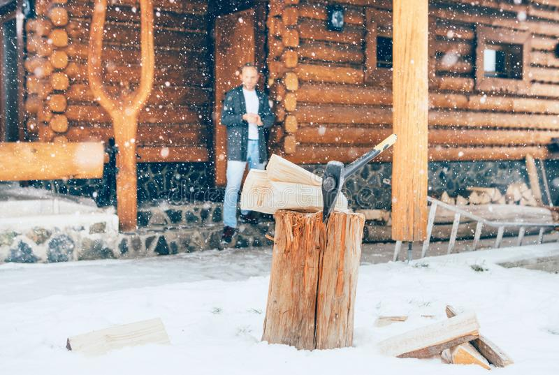 Man staying in the country house porch. Wooden stump with axe on snowy yard unfocused with heavy snowflakes . Winter countryside h stock photography