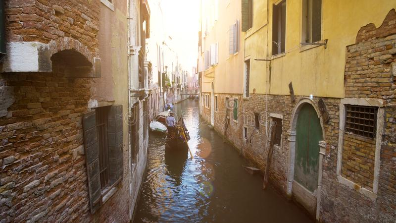 Man steering old gondola boat in narrow street of Venice, romantic trip to Italy royalty free stock photos