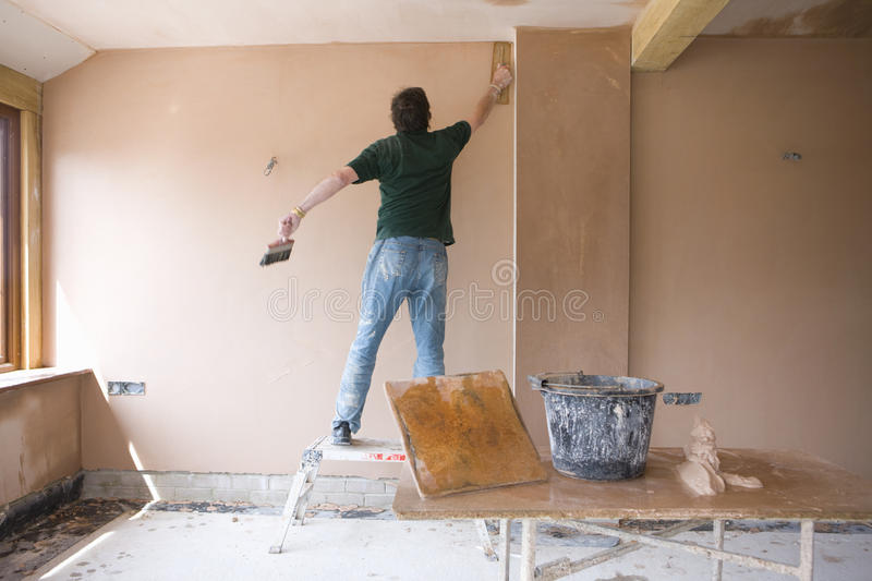 Plaster Wall Construction : Man on step stool plastering wall in house under