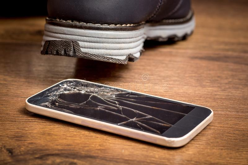 The man stepped on a cell phone and damaged the glass. A broken mobile phone needs to be repaired_. The man stepped on a cell phone and damaged the glass. A royalty free stock photography