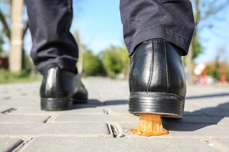 Man stepping in chewing gum on sidewalk. Concept of stickiness stock images