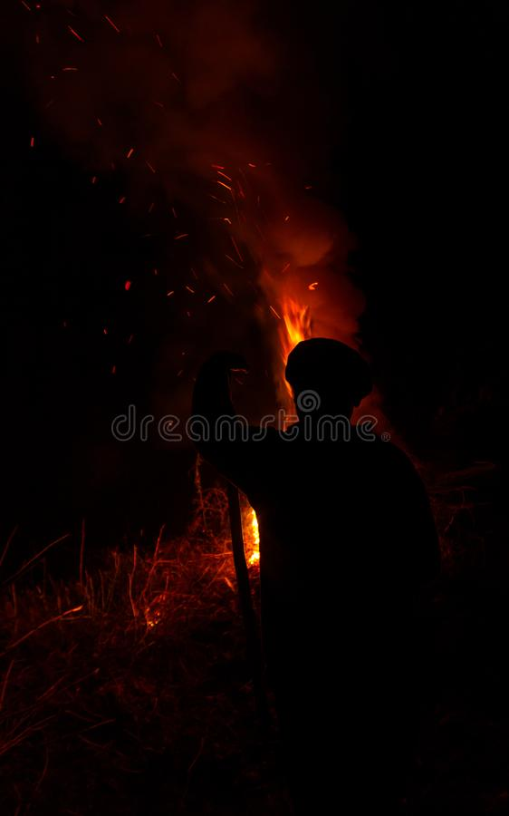 Man with stick silhouette burning dry grass at night. Man with stick silhouette looking at fire at night stock photos