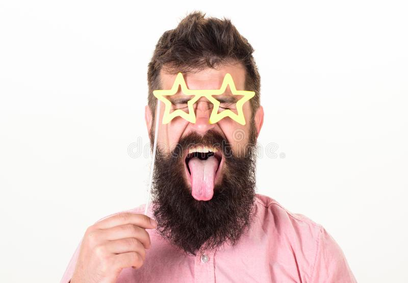 Man with stickout tongue, closed eyes and beard wearing paper star shaped glasses, fun concept. Hipster with crazy look royalty free stock photography