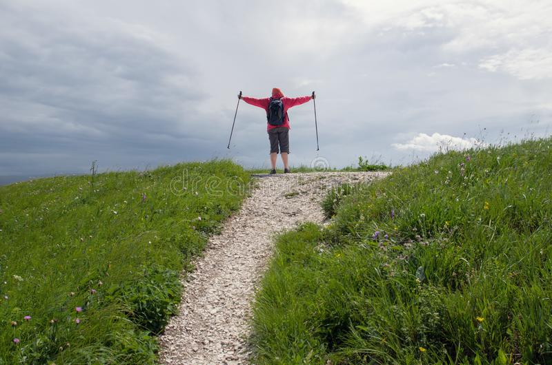Man with sticks for Nordic walking rejoices at the top of the mountain. Outdoor royalty free stock photography