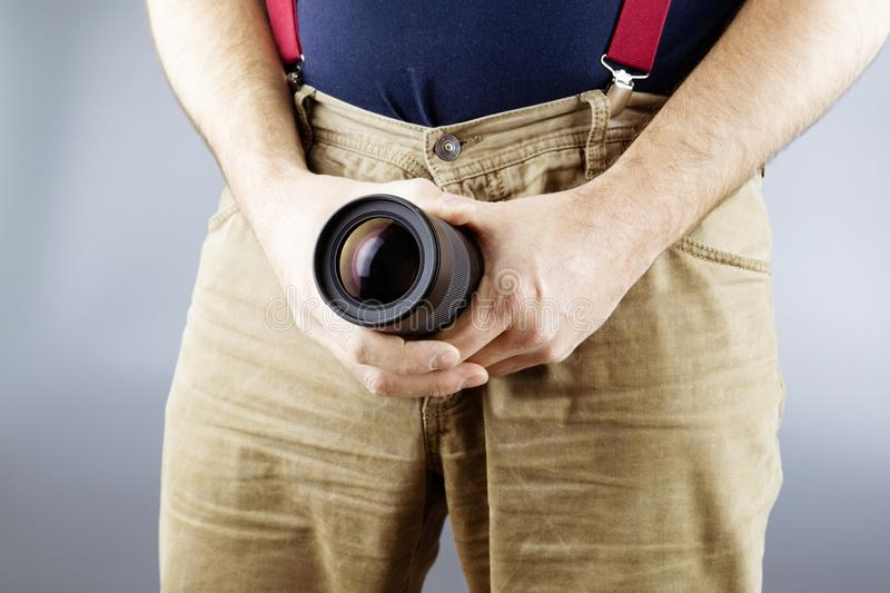 The man sticks out the lens of his pants, a large lens and yellow pants on. A gray background royalty free stock photos