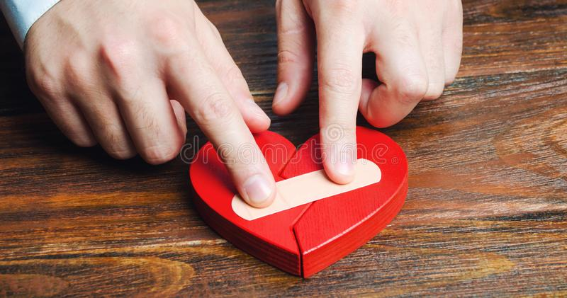 A man sticks together a red heart with a plaster. Renewal of the relationship. Family psychotherapist services. Reconciliation. stock photos