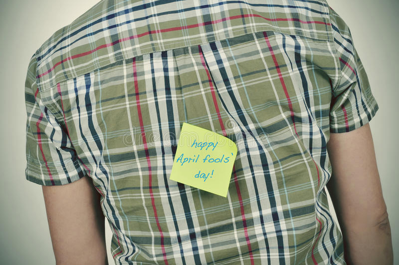 Man with a sticky note with the text happy april fools day stock image