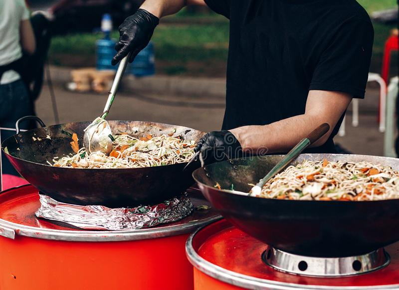man stiring pasta with vegetables and seafood at street food festival. chef with gloves cooking traditional italian macaroni dis stock photos
