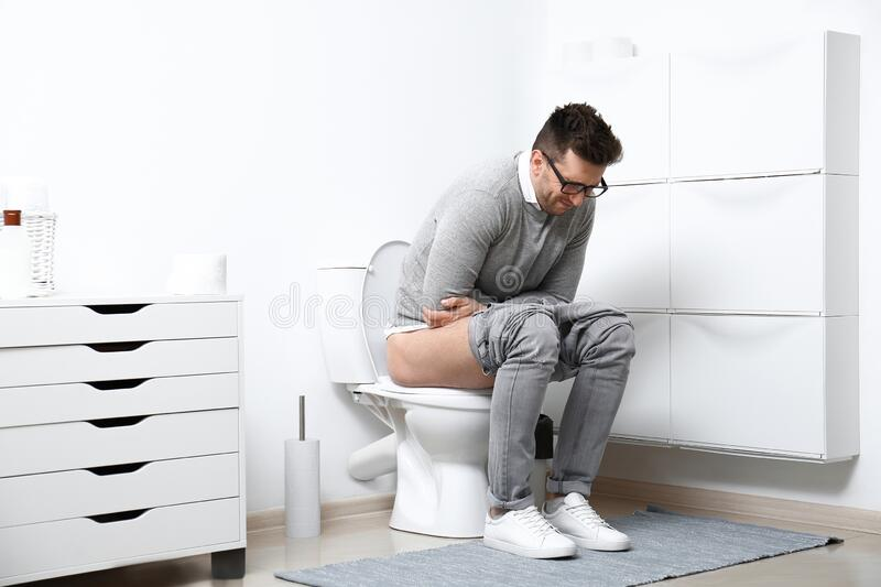 Man with stomach ache sitting on toilet bowl stock images
