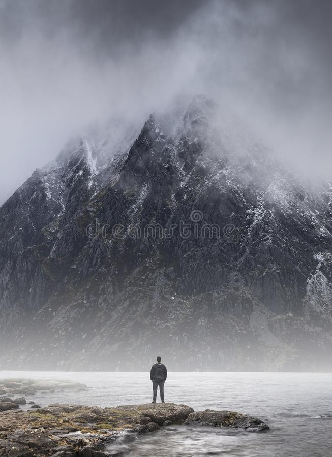 Man stood in front of foggy misty mountain to give scale of mountain size and concept of overpowering challenge. Man stood on lake shore dwarfed by mountain in royalty free stock photography