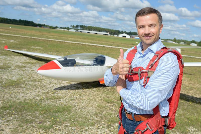 Man stood by glider giving thumbs up royalty free stock images