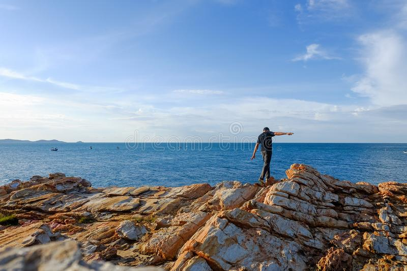 Man stands his arms on a rock. Man stood on a rock by the sea at Khao Laem Ya, Rayong, Thailand stock photography