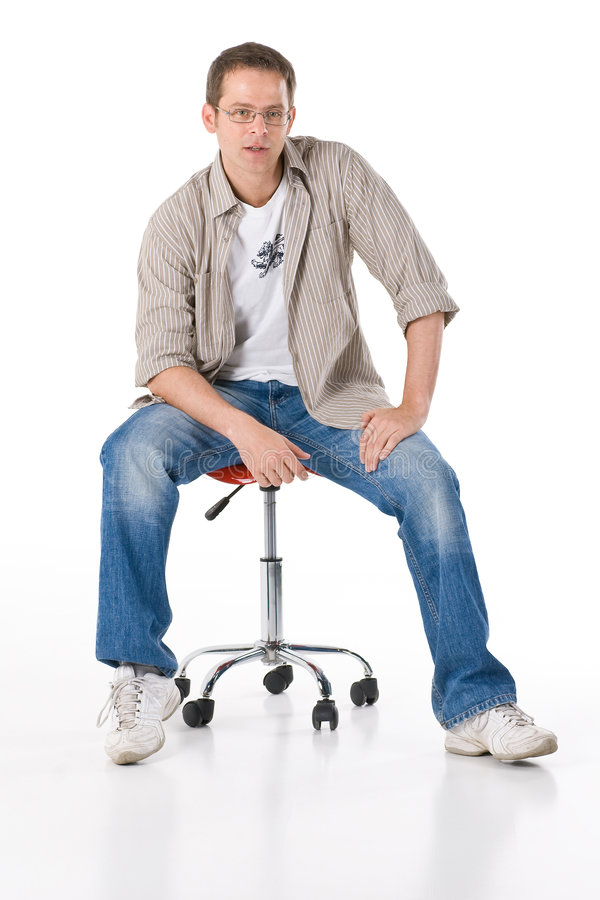 Man on stool. Man sitting on a stool with wheels stock image