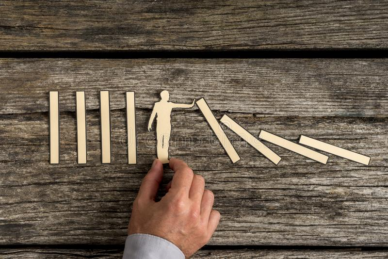 Man stopping the domino effect with a paper cutout silhouette stock photography