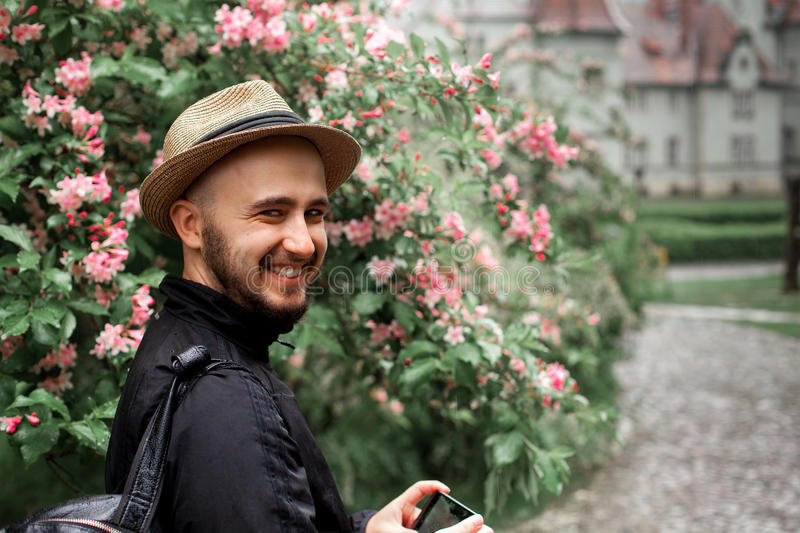 Man in a straw hat and with a beard looking at the camera and sm. Handsome young man in a straw hat and with a beard looking at the camera and smiling on a royalty free stock photos