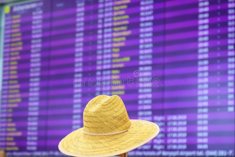 A man in a straw hat is standing in front of a blurred information board for arrivals and departures. Information stand royalty free stock image